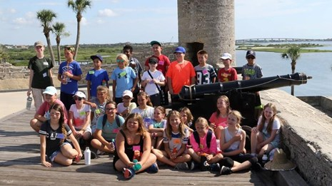 Field trip of students on gun deck near cannon and bell tower.