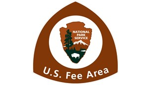 U.S. Fee area triangular sign with NPS Arrowhead centered