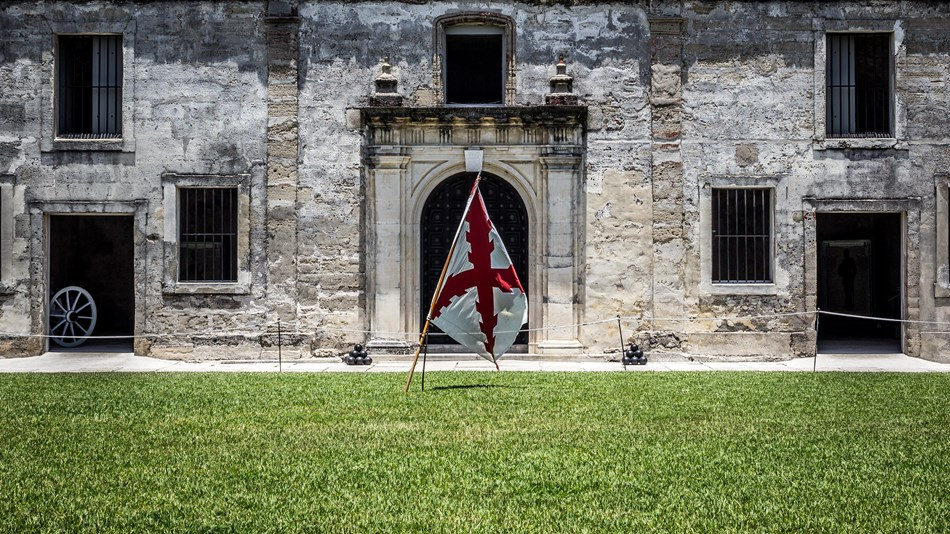 Grass in foreground, splanish flag centered in image, chapel door and walls in background
