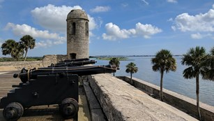 Image of gun deck with cannons, bell tower, water, and palm trees.