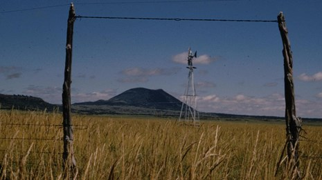 Capulin Volcano, in the distance, is framed by gate posts and a windmill from the plains.