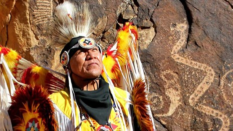 Native American in colorful ceremonial dress.