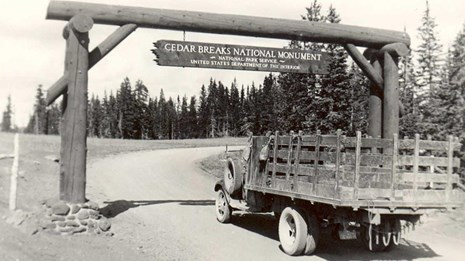 Old truck driving under wooden sign saying
