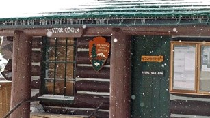 Snow falling in front of old log cabin.