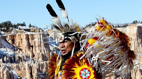 Close up of older native american man with ceremonial dress & orange cliffs in the background.