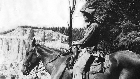 Black and white photo of a man on horseback, looking out at a rocky landscape.