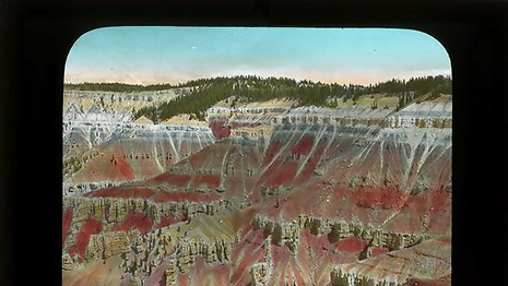 Old color slide image of Cedar Breaks cliffs - hand painted in pink and orange.