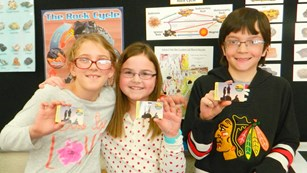 Three kids holding their fourth grade park passes.