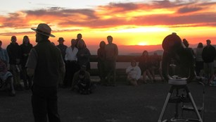 People and telescope silhouetted against a sunset.