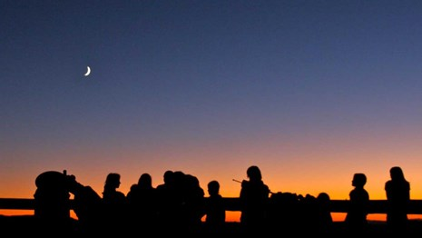 Silhouetted people, moon and Venus against a sunset.