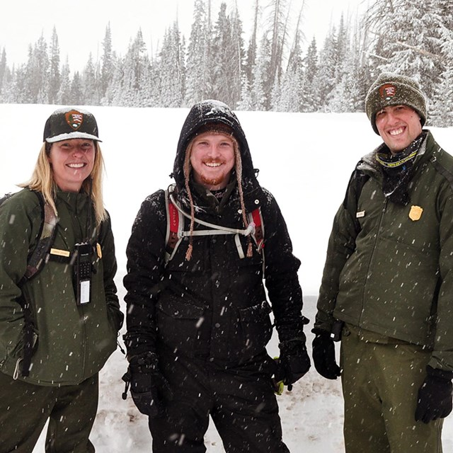 Three park employees dressed for winter standing in-front of a snowbank.