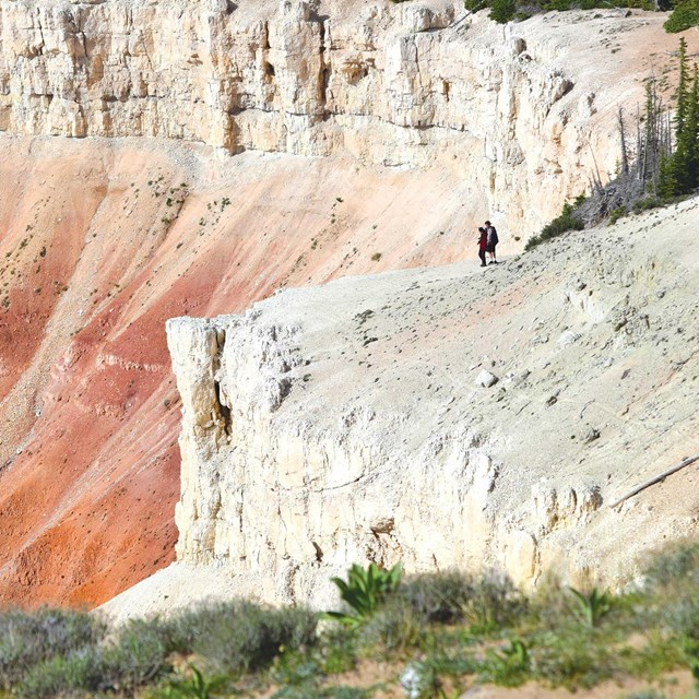 Two hikers standing on the edge of a very large steep white cliff.