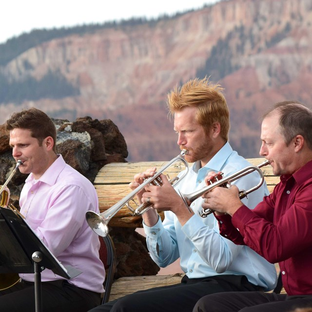 Three men playing brass instruments in front of red and white cliffs.