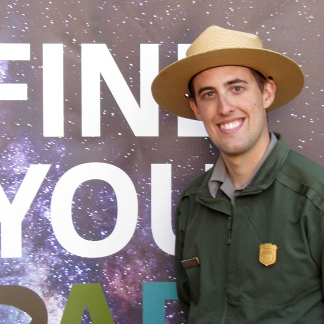 Male park ranger standing in front of sign reading Find Your Park.