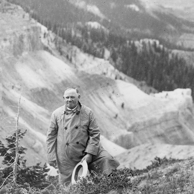 Black and white photo of man posing before a landscape.