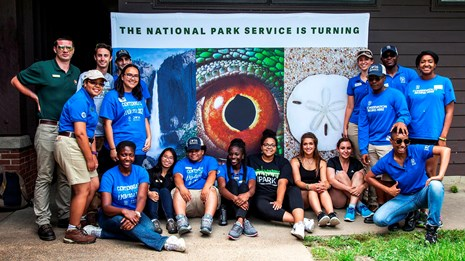 Young adults gathered around in front of a centennial banner.