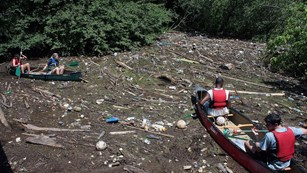 Two canoes surrounded by trash in the river during one of many river cleanups.