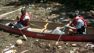 Two Volunteers sitting in a canoe picking trash out of the river.