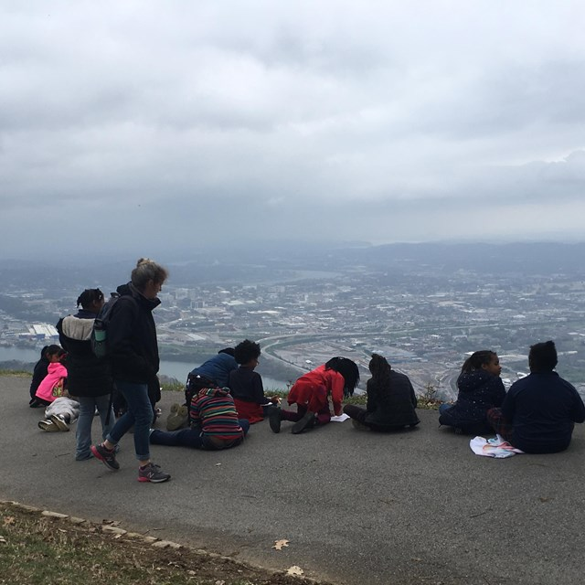 Students overlooking a city from a sidewalk