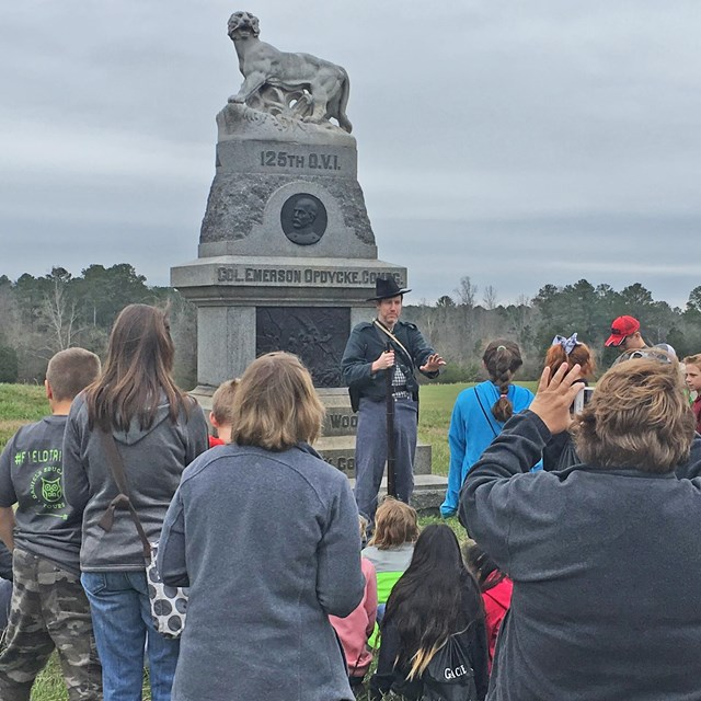 A man dressed in Civil War uniform talks to students in front of a monument