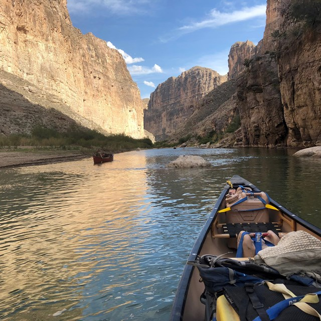 Two canoes navigating the Rio Grande River channel.
