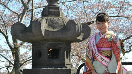 A Japanese woman in cultural attire stands in front of a Japanese stone lantern