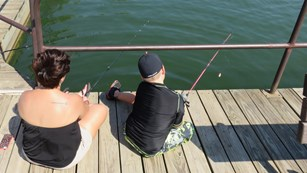 Two people sit on a dock, holding fishing rods.