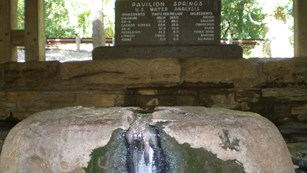 Water flows up out of a rock. An old wood routed sign details the mineral content of the water.
