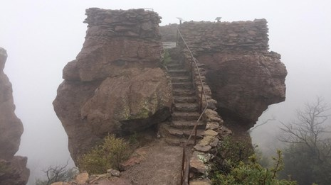 Stone steps leading to a platform on a large rock, in the fog.