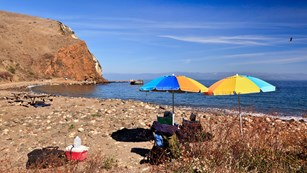 Visitors sitting on beach with umbrellas. ©Tim Hauf, timhaufphotography.com