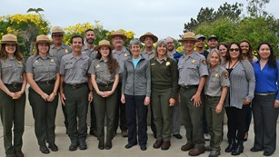 Park rangers standing in front of yellow flowered plant.