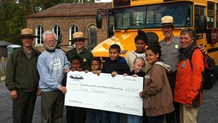 Rangers pose with students holding scholarship check