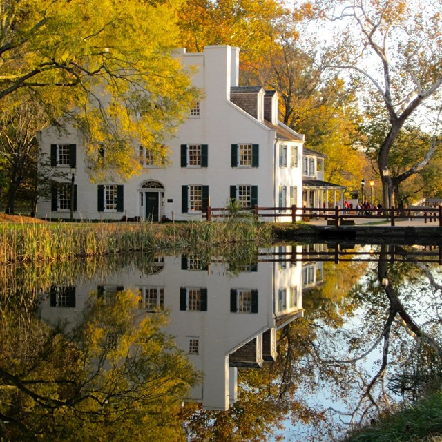 Great Falls Tavern Visitor Center in autumn reflecting in the watered canal.
