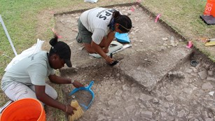 Photo of archeologist and student intern excavating remains of historic building at Christiansted.