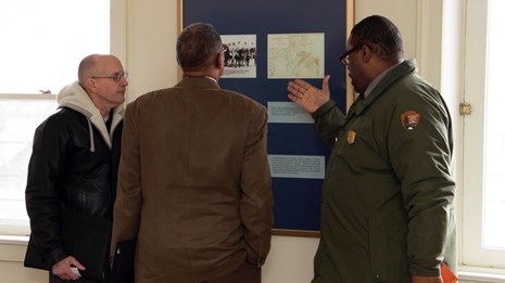 Three men gathered around a wall information panel in a discussion.