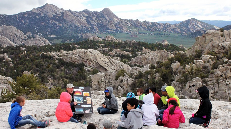 A group of children sit on a rock while listening to a Ranger presentation.
