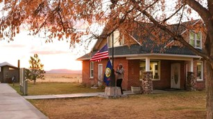 A ranger is taking down the American flag and the Idaho state flag at the end of the day.
