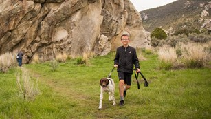 A boy with a dog on a leash hikes through the City of Rocks