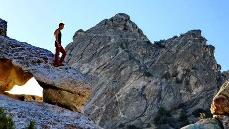 A person walks along the top of a granite formation.