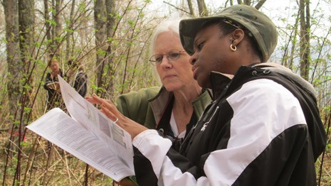 two women examine a pamplet in a forest setting