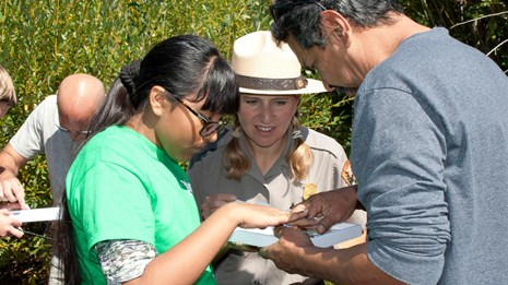 A ranger helps two people sort a specimen tray.