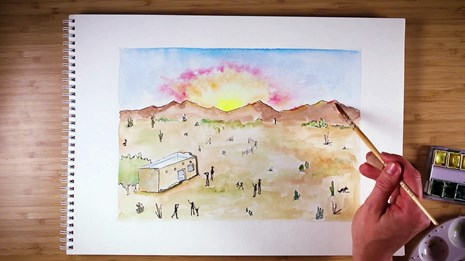 View of notebook paper with hand holding watercolor brush, painting a desert sunset image