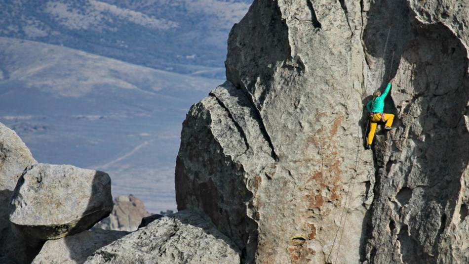 A colorful female climber ascends granite rock called the Anteater in City of Rocks National Reserve