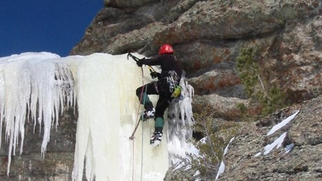 Male ice climber ascending a frozen waterfall