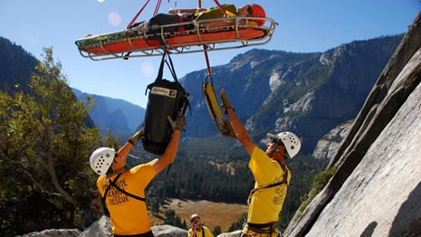 Search and Rescue crew coordinates with helicopter lifting patient from rock face