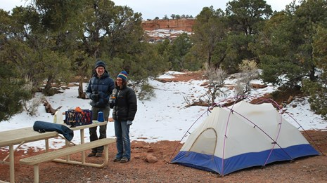 2 people by tent with snow on ground. Some sites are available by reservation March - October.