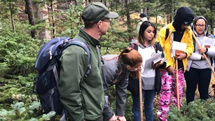 Students learn about forest monitoring from ranger in the field.