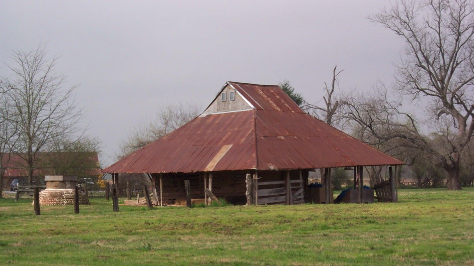 Farm building with large, sloping, rusted tin roof