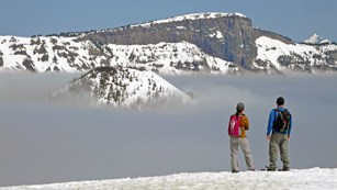 Two snowshoers gaze at the lake, filled with fog.