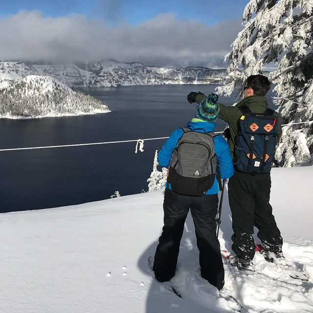 Snowshoers view the lake from behind a rope which indicates the rim edge